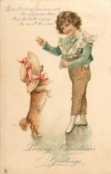 LOVING CHRISTMAS GREETINGS  boy holds cracker for begging dog wearing bonnet standing on hind legs