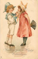 WISHING YOU A HAPPY CHRISTMAS  boy adjusts hat ribbon of girl who has fan held behind her