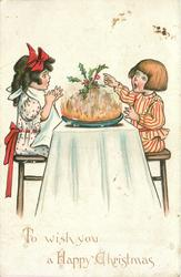 TO WISH YOU A HAPPY CHRISTMAS  boy & girl sit amazed on either side of table with Xmas pudding between them