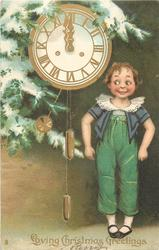LOVING CHRISTMAS GREETINGS  boy in green suit with grey top stands to right of clock