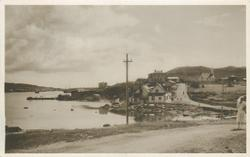 street view, pylon in middle, sea behind, houses on right, white dressed woman