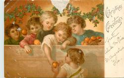 CHRISTMAS GREETINGS 5 children behind wall one hold orange down to girl below