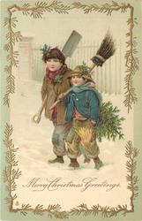 MERRY CHRISTMAS GREETINGS  two boys, one has tree & broom, the other a shovel, walk in snow **