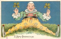 A MERRY CHRISTMAS TO YOU  clown with legs widely spread, holding two 4 leaf clover