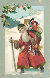 A MERRY CHRISTMAS Santa with green cap & sack of toys walks left with cane