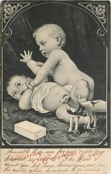 A MERRY CHRISTMAS TO YOU  two babies wrestle on floor, toy dog on wheels front
