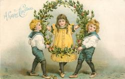 A HAPPY CHRISTMAS  girl in yellow stands in holly wreath held up by two boys in sailors outfits