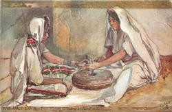 TWO WOMAN GRINDING AT HAND MILL