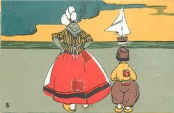 woman & boy facing away looking at sailing boat on sea