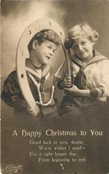 A HAPPY CHRISTMAS TO YOU two boys, boy on left holds large fake horseshoe and wears dark coloured sailor shirt