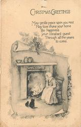 CHRISTMAS GREETINGS  cottgae scene, woman sits by fireplace with two black cats