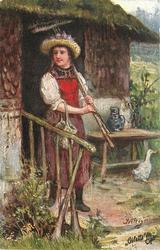 ZUR ERNTEZEIT  woman in red apron with rake on shoulder stands in cottage doorway