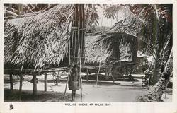 VILLAGE SCENE AT MILNE BAY woman standing below entrance to hut