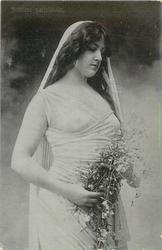 actress stands facing half right holding flowers