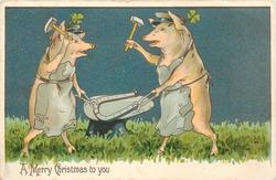 A MERRY CHRISTMAS TO YOU 2 pigs as blacksmiths hammer horseshoe on anvil, 4 leaf clover above each