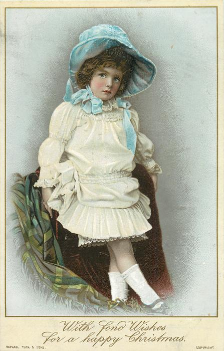 girl in white dress with blue bonnet stands wtih feet crossed, blanket to left