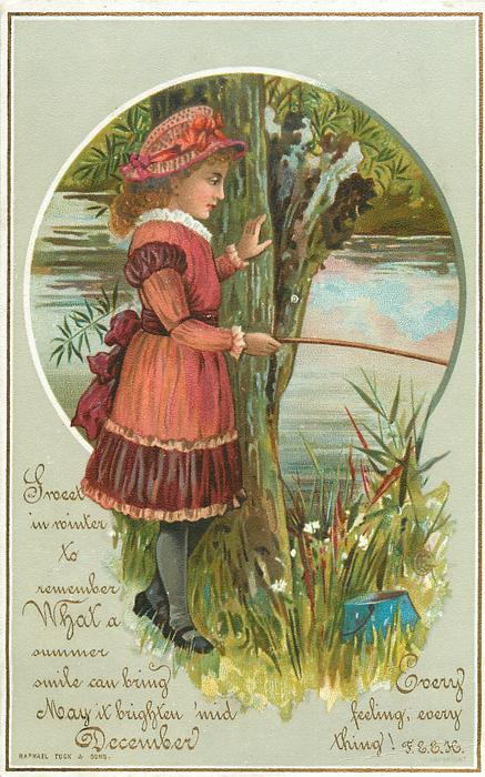 girl in red dress stands by tree at shore and holds fishing rod