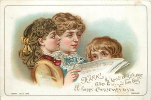 three children  hold songbook and sing