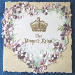 THE DIAMOND REIGN gold crown within heart shaped wreath of purple and white flowers