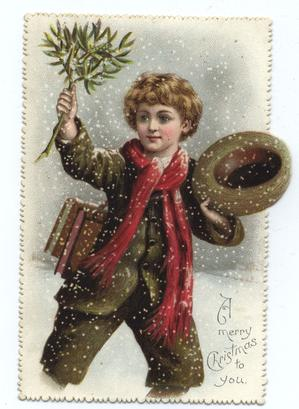 young man with red scarf holds up mistletoe in his right hand and a hat in his left