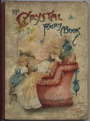 THE CRYSTAL FAIRY BOOK mother in chair reads to child sitting on stool at her feet