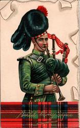 Scotsman in green uniform plays bag-pipes, AULD LANG SYNE on tartan at base