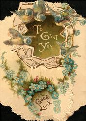 TO GREET YOU on green plaque, 4 blue-birds above, garlands & horse-shoe of blue forget-me-nots, GOOD LUCK below