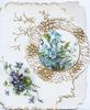 no front title, perforated gilt & white circular design with inset forget-me-nots, more flowers below right
