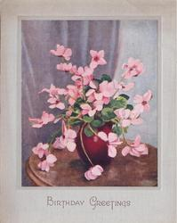 BIRTHDAY GREETINGS pink cyclamens in red pot on circular table