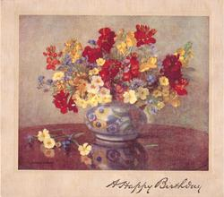 A HAPPY BIRTHDAY opt. in gilt, multi-coloured primroses in floral patterned vase, scattered flowers & reflection on table