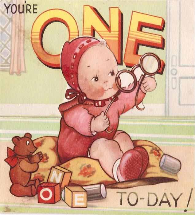 YOU'RE ONE TO-DAY baby in red onesie & bonnet holds up glasses, blocks spelling ONE & teddy left