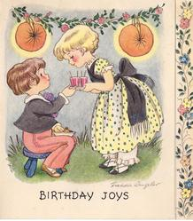 BIRTHDAY JOYS girl offers cup to boy sitting on stool, floral garland with orange lanterns behind, floral panel right