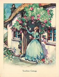 SUNSHINE COTTAGE woman in  blue dress faces left & looks up, reaches for flower that overhangs cottage door