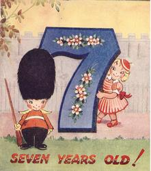 SEVEN YEARS OLD! boy dressed as royal guard left of large blue 7 with stylised flowers, girl peeks from behind