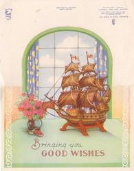 BRINGING YOU GOOD WISHES miniature sailing ship on table, small vase of pink flowers left, window behind