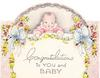 CONGRATULATIONS TO YOU AND BABY baby wearing pink holds yellow ribbon, large blue bow, roses & yellow flowers on either side