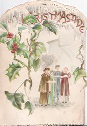 CHRISTMASTIDE in  red on white background, vertical holly & ivy, 4 choristers stand singing front right