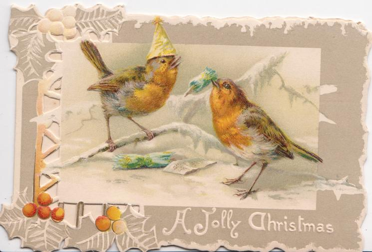 A JOLLY CHRISTMAS in white, two robins in winter, one wears a white hat, the other has christmas cracker in beak, in holly bordered panel