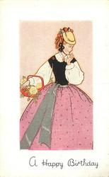 A HAPPY BIRTHDAY woman in large dotted pink skirt with grey sash, faces front, looks right, holds basket of flowers in right arm