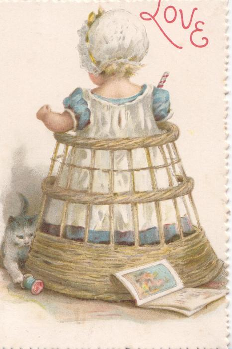 LOVE in red, young girl in old style dress stands in wicker play-pen, faces back, kitten left