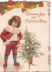 CHRISTMAS JOYS AND CHRISTMAS TOYS child in old style dress talks to personised Christmas tree