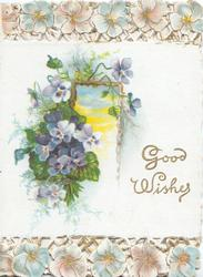 GOOD WISHES in gilt, white & purple pansies left of framed view of sky,  pansies over perforated lattice design top & bottom