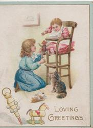 LOVING GREETINGS in gilt, girl in blue shows puppet while kneeling before child in high chair