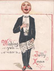 WISHING YOU A JOLLY XMAS(W,J &X illuminated), singer in evening dress stands facing front