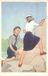 no front title, two girl guides climb rocks at water's edge