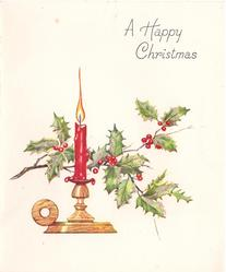 A HAPPY CHRISTMAS glittered holly sprig behind lit candle on candlestick
