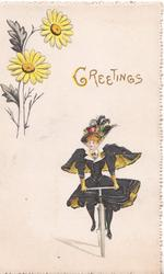 GREETINGS in  gilt above lady in black riding bicyle front, yellow daisies upper left