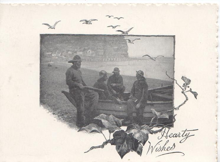HEARTY WISHES, sea, shore & village behind 4 fishermen aroiund beached boat, ivy around