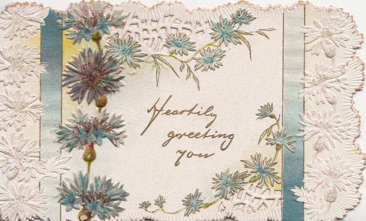 HEARTILY GREETING YOU in gilt surrounded by blue cornflowers, 2 blue ribbons & heavily perforated white design
