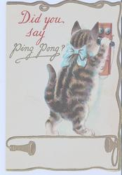 DID YOU SAY PING PONG? cat with blue bow stands facing old telephone, piece held to ear